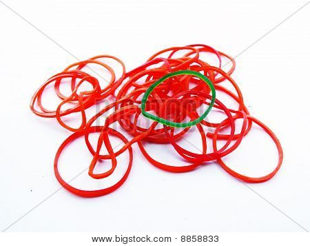 A green Elastic rubber on many Red Elastic rubber isolate on white background
