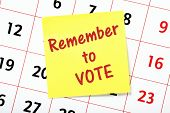 Remember To Vote reminder on a yellow sticky note attached to a wall calendar poster
