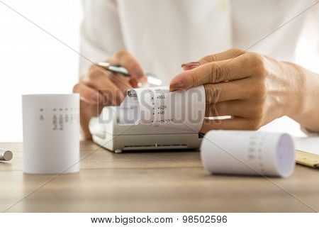 Woman Doing Calculations On An Adding Machine