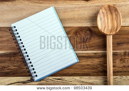 Open recipe book - notebook and wooden spoon on wooden background