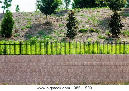 Block Retaining Wall Topped With Black Iron Fence