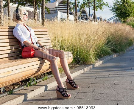 Fashion leggy girl in a beautiful high-heeled shoes in short denim shorts in the summer sitting on t