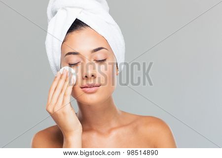 Portrait of a charming woman with towel on head holding wadded disk over gray background