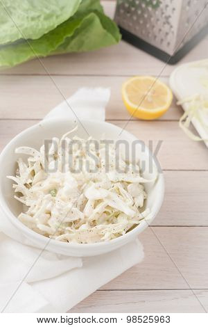 white cabbage cole slaw in white bowl