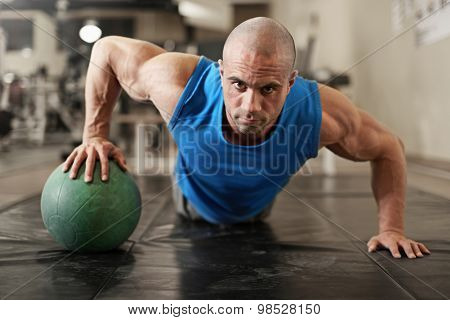active and muscular man keeping fit by doing pushups using a medecine ball - filtered image