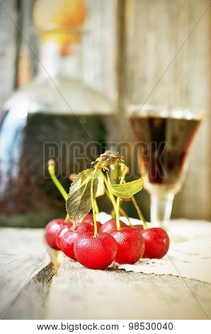 Cherry liquor in the little glasses and big bottle on the vintage napkin on the old wooden background poster