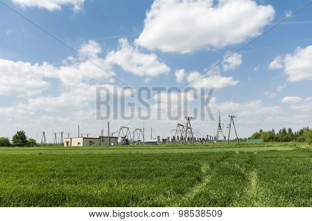 Electrical substation among green fields and bushes poster