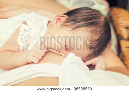 Soft focus image of newborn baby breastfeeding