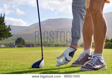 golf man placing ball pin for tee shot on vacation