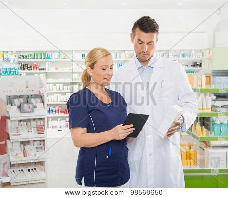 Female assistant using digital tablet while male pharmacist holding product in pharmacy