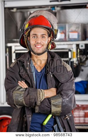 Portrait of smiling firefighter standing arms crossed against firetruck at station