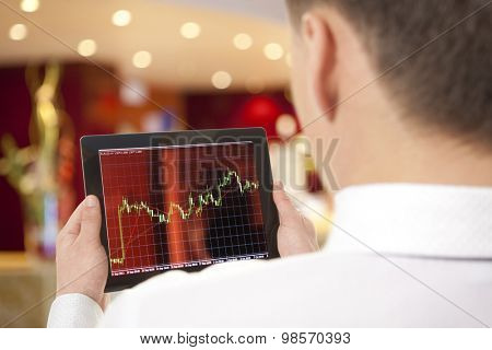 Businessman checking the stock market on digital tablet in office