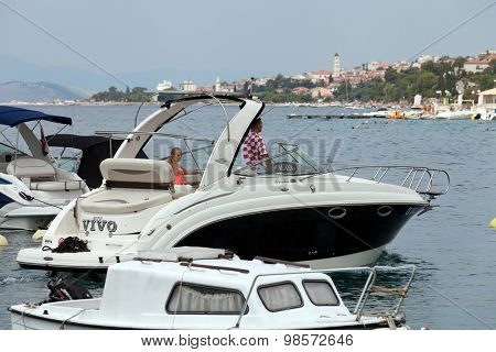 SELCE, CROATIA - JULY 24, 2015: A boy and a girl in the powerboat sailing our of Selce Marina