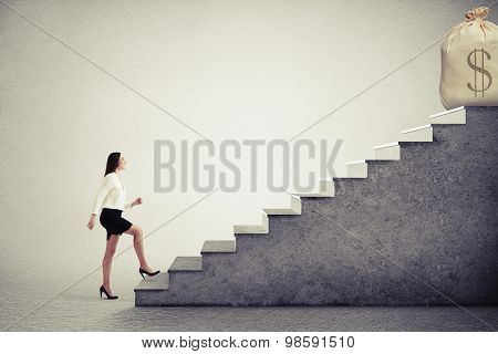 smiley businesswoman rising up stairs and looking at big bag with money on the top over grey background