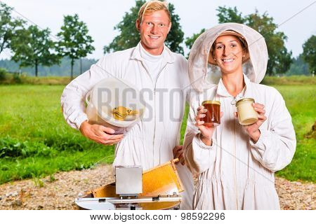 Beekeeper filling honey with extractor in glass