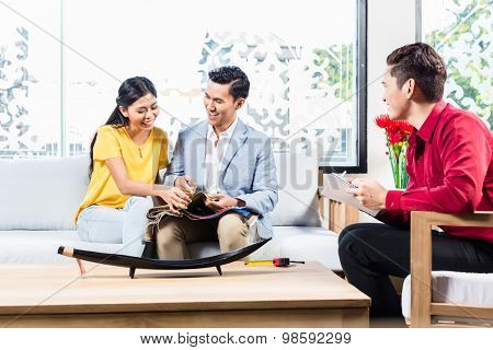 Couple with shop assistant in Asian furniture store