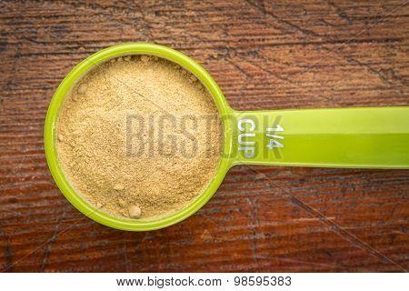 maca root powder on a measuring scoop against rustic wood