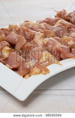 Raw Skewer Meat On A White Plate Over Wooden Background
