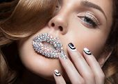Beautiful girl with bright nails and lips of crystals, long eyelashes and curls. Beauty face. Picture taken in a studio. poster