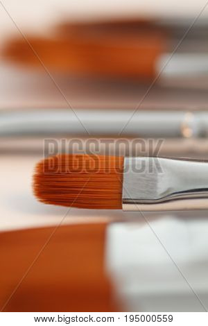 Artistic brushes macro. Brushes artist on an abstract blurred background in the studio for artists.