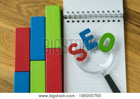Search engine optimisation concept as colourful alphabet SEO on magnifying glass on note paper and wooden block  chart on wooden table.