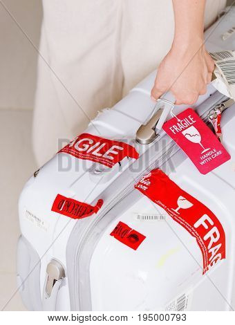 Nha Trang Vietnam - August 16 2016: Man holding suitcase in hand at airport of Cam Ranh. Red luggage tag (Fragile Handle with care) attached to white plastic suitcase.
