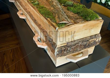 A coffin made of natural wood covered with moss on top in a morgue