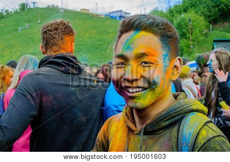 Moscow, Russia - June 3, 2017: Portrait of asian teenager boy with face stained with bright colors after massive traditional summer celebration of Holi. Indian festival Holi turned into a fun event