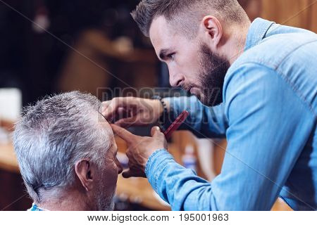 Male haircut. Nice handsome bearded barber standing in front of his client and holding a comb while doing a new haircut
