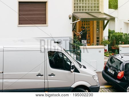 PARIS FRANCE - JUL 12 2017: Young delivery man holding cardboard parcel box ringing at the doorbell and waiting the consignee to open the door and put the signature in clipboard