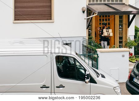 PARIS FRANCE - JUL 12 2017: Young delivery man holding cardboard parcel box knocking ringing at the doorbell and waiting the consignee to open the door and put the signature in clipboard
