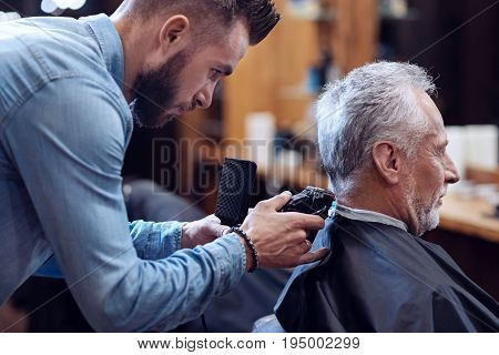 Modern hairstyle. Professional experienced bearded barber holding a comb and using a hair cutting machine while making his client a haircut