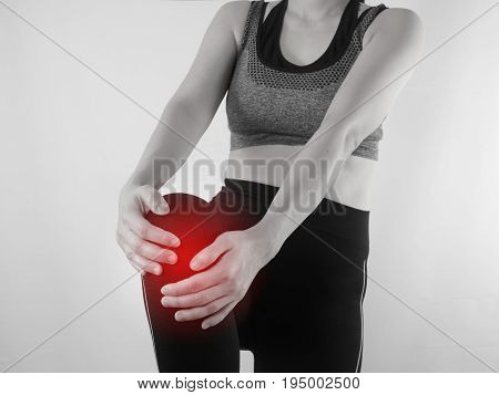 Young Asian woman in workout cloth holding knee and having knee ache with red focus dot on isolated background.