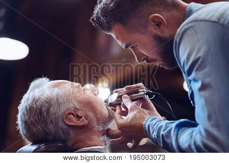 Beard trimming. Serious confident professional barber holding an electric shaver and trimming his clients beard while doing beard styling