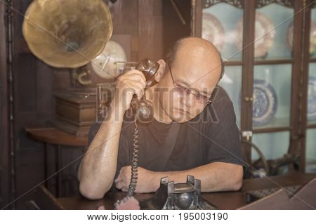 Male hands using and dialing a vintage telephone