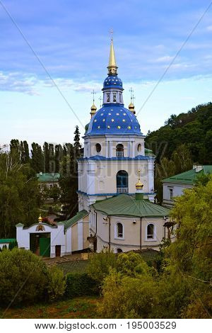 Blue dome of Vydubitsky monastery in Kiev on the beautiful sky background. The plane fly near the dome. Warm summer evening