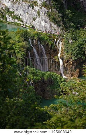 PLITVICE LAKES - CROATIA - JULY 2005: Waterfalls in National park Plitvice in Croatia. Waterfalls surrounded by forests. Tourists walk in the park. Vertical photo