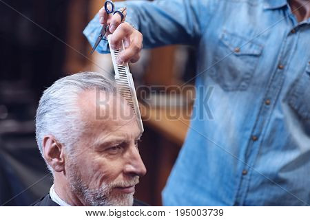 Professional comb. Nice professional male barber holding scissors and combing his customers hair while doing a haircut