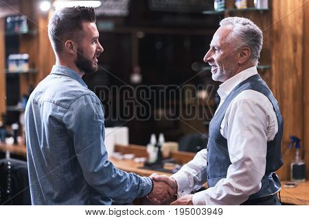 Thank you. Positive delighted grateful man smiling and looking at his barber while being happy with his new hairstyle