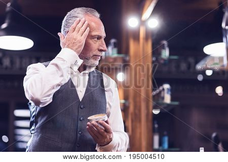 Hair care products. Handsome nice senior man looking into the mirror and using a hair gel while styling his hair