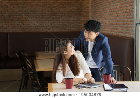 Business partners are discussing financial issues happily./Asian Business couple in love at a coffee shop, they are smile. Conception in coffee shop.