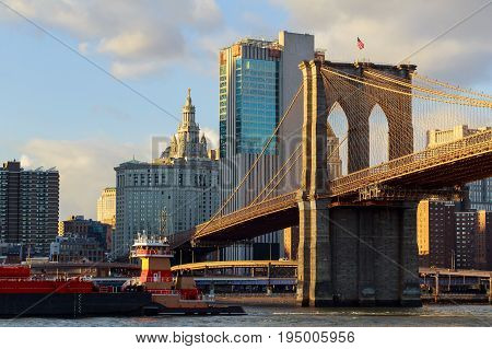 The Brooklyn Bridge stands against a blue sky downtown Manhattan skyscrapers