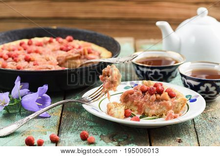 Homemade rhubarb pie in cast iron skillet with fresh wild strawberries on shabby turquoise boards with tea and bellflower closeup