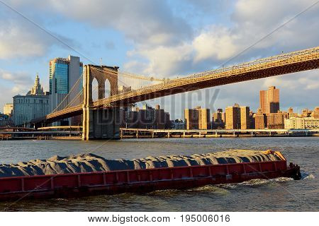 The barge floats along the Hudson River in the background of the Brooklyn Bridge The Brooklyn Bridge with the lower Manhattan in the background New York,