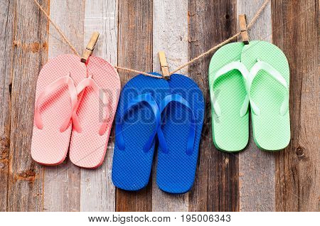 Pink, Blue And Green Flip Flop Sandals On Wood Background