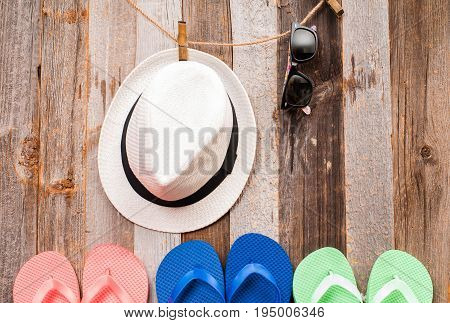 Hat, Sunglasses And  Flip Flop Sandals On Wood Background