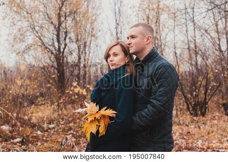 Affectionate cozy hugs of young loving couple in the autumn park