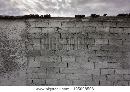 The Old Brick And Stone Wall With Roof Against Sky