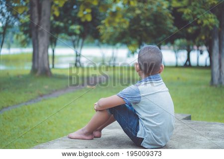 yong asian boy stay Alone and scared in the park