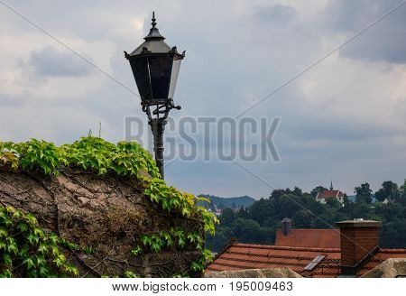 Street Lantern And Stone Wall Against Sky